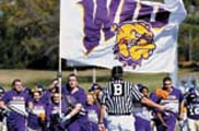 Photo of cheerleaders with WIU flag at a football game